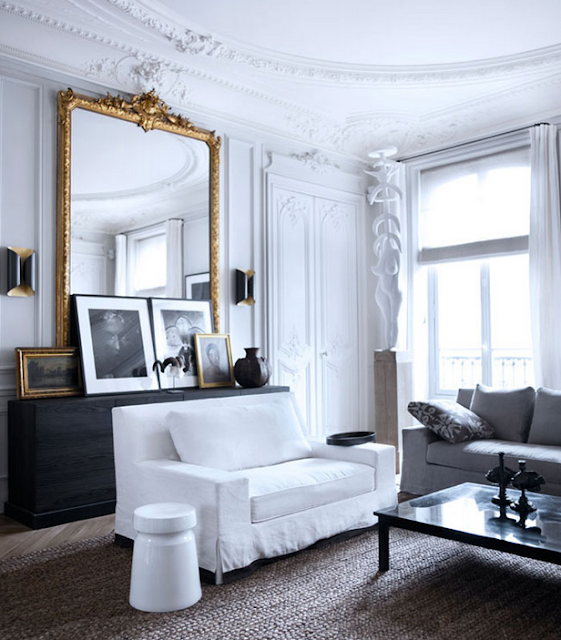 Gilles & Boissier design living room with golden mirror black and white art and jute rug and slipcovered sofas  via belle vivir blog