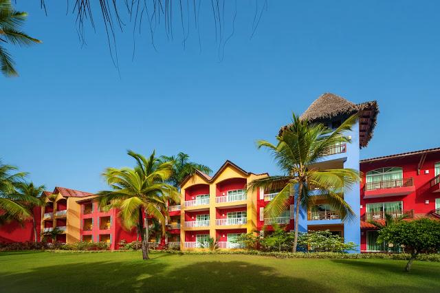Entrée de l'hôtel avec facades colorées: bleu, jaune, rouge dans un jardin tropical avec cocotiers
