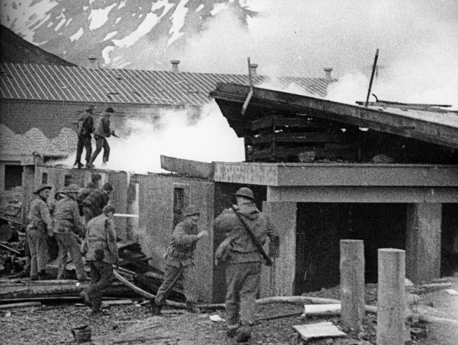 U.S. soldiers fight a fire after an air raid by Japanese dive bombers on their base in Dutch Harbor, Alaska, in June 1942.