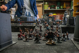cultists lead by a dark apostle advance across the battlefield