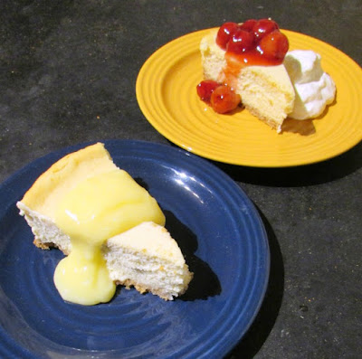 cheesecake slice served with lemon curd and one served with cherries and whipped cream