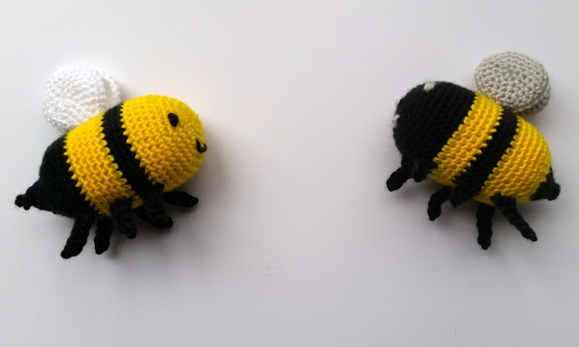 Side views of the two bees. The yellow-faced, white-winged bee on the left and black-faced, silver-winged bee on the right, facing each other.