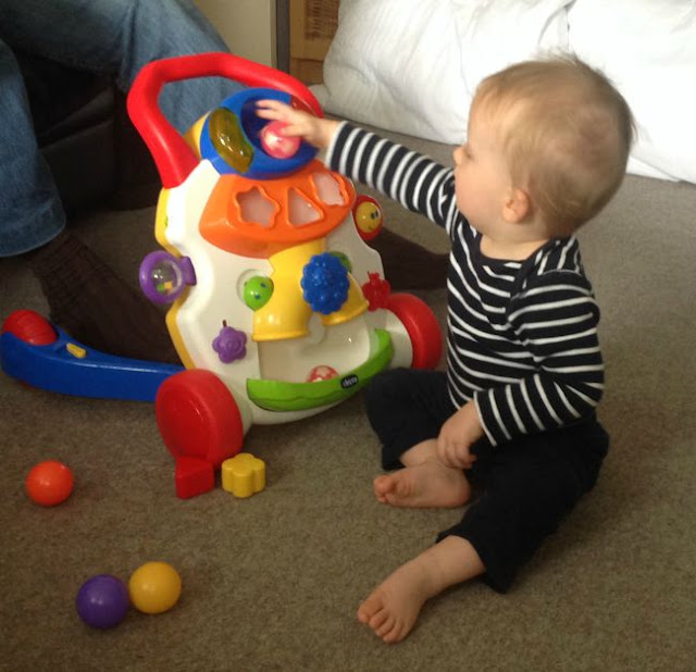 Baby putting ball into hole in toy