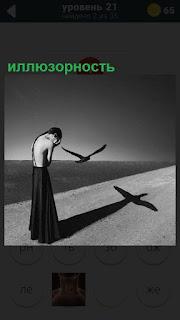 Стоит человек и летит птица, а на падающей тени образовался крест