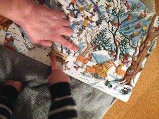 Im Weihnachtswimmelbuch gucken wir uns die Tiere. Dabei zeigt das Kind auf eine Vogelfutterstelle.