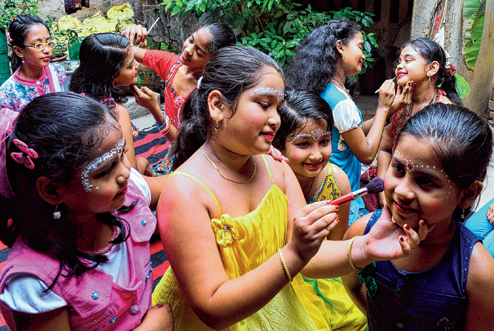 Young girls embellishing each other with sandalwood tikkas during Raja