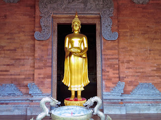 Standing Buddha Statue Carrying Jug In Front Of The Door At Brahmavihara Arama Monastery North Bali