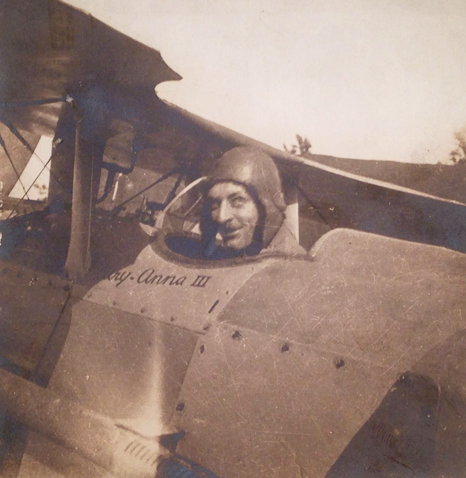 A photograph of a man's head peaking out of a small airplane.