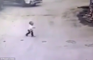 Child in China escapes being run over by truck