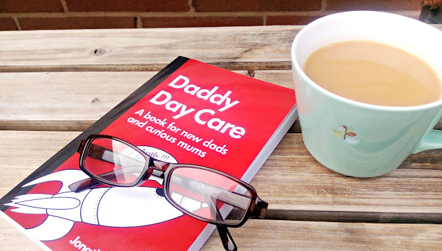 Daddy Day Care book, resting on a bench with a cup of tea and some reading glasses.