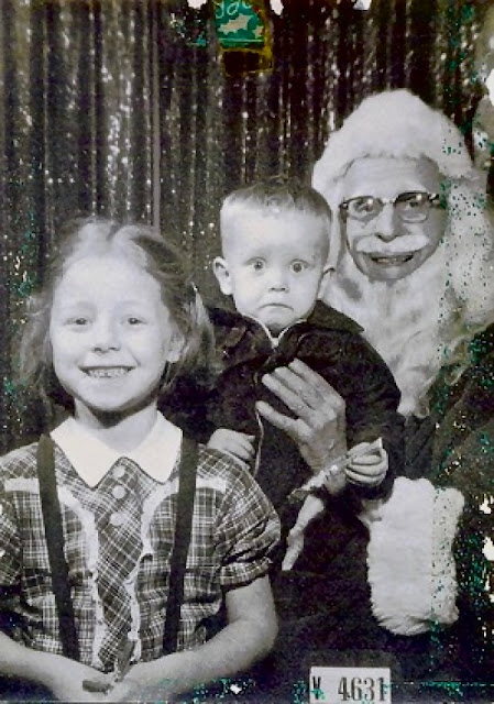 Sister and little brother photo with mall santa. Little brother looks distressed. c.1950s. A Pleasant Christmas Story and other stories of Christmas Creepers. marchmatron.com