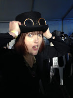 Girl holding onto a top hat on her head and looking surprised