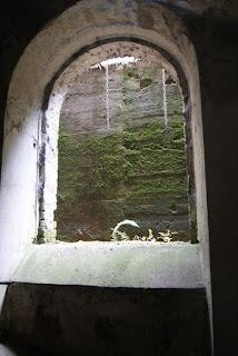Ein Rundbogenfenster ohne Fensterglas, durch das Licht in einen Raum fällt