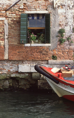 red boat on Venetian canal