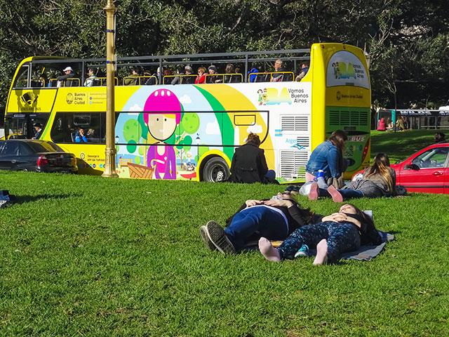 Sobre el césped gente recostada al sol y al fondo turista en bus esperando.