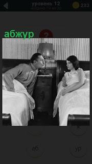 в спальне находятся двое на разных кроватях и в середине абажур на лампе