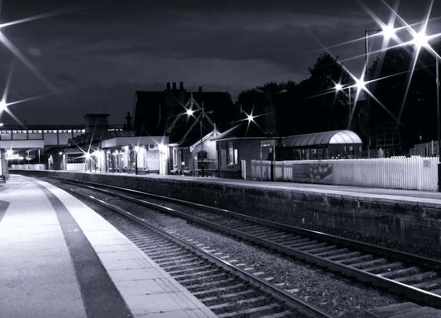 Black and white night photo taken in late evening of platform 1 and main station building