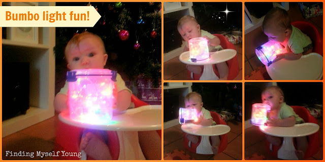 Baby playing with christmas lights while sitting in a bumbo