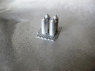 Four modern dolls' house miniature spray cans, painted silver.