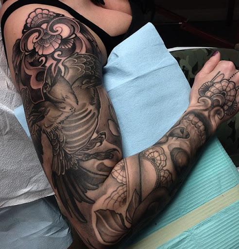 Em tons de cinza de manga tatuagem sobre corvos. Você pode imediata e o corvo voando alto e forte sobre a parte superior dos braços. Você também pode ver um pouco de floral design, bem como alguns temas tribais também.