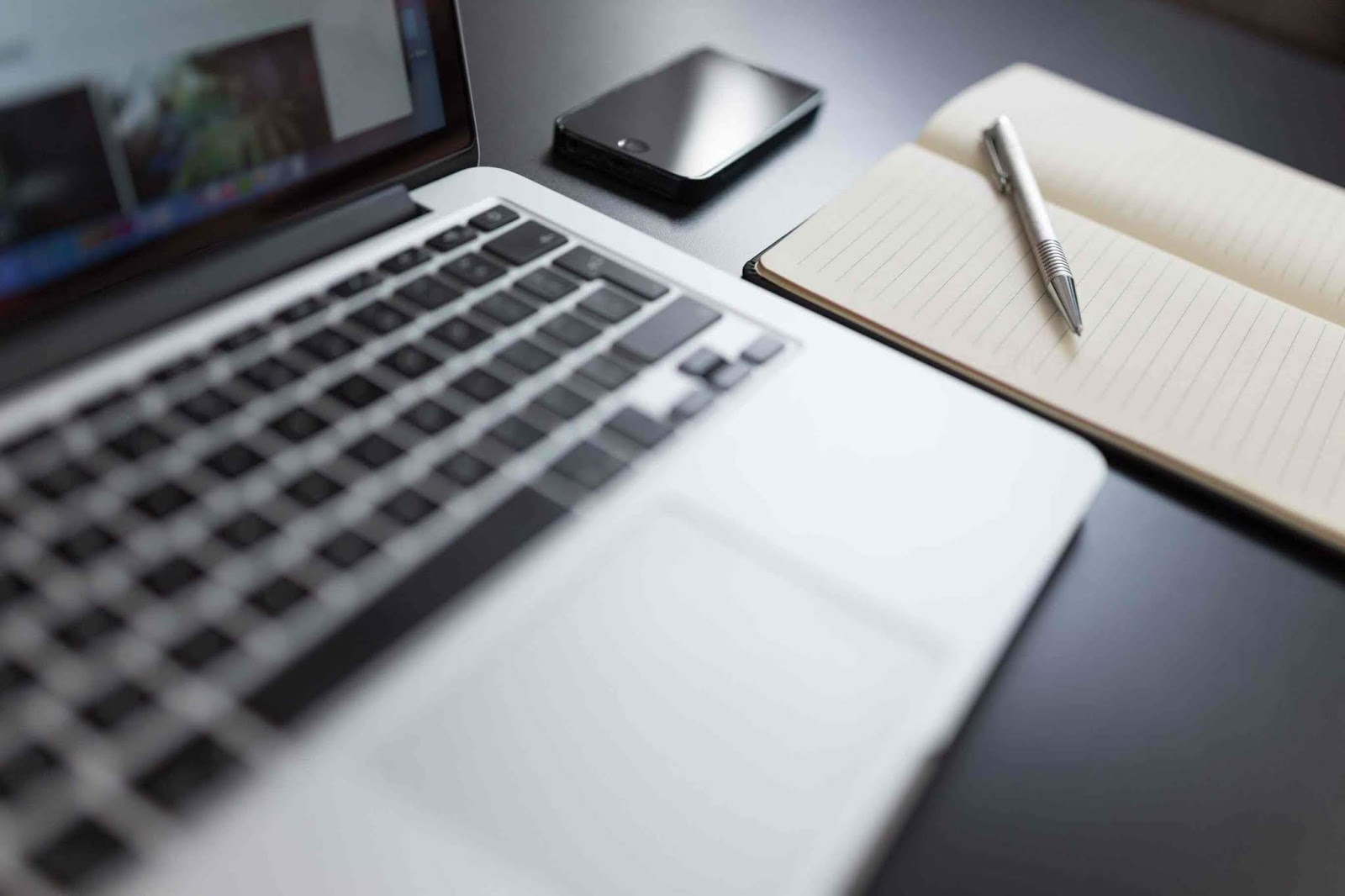 Black and white photo of a laptop, a notebook, a smartphone, and a pen