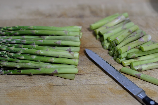 The asparagus on a cutting board with the woody ends trimmed off.