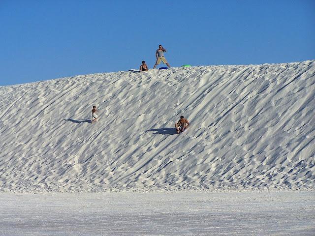 Des gens qui font de la luge dans la sable blanc :D