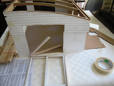 Half-built dolls' house shed with weatherboard cladding attached and a sliding door in pieces in the door frame.