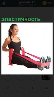 Женщина в спортивном костюме использует резиновый бинт на эластичность
