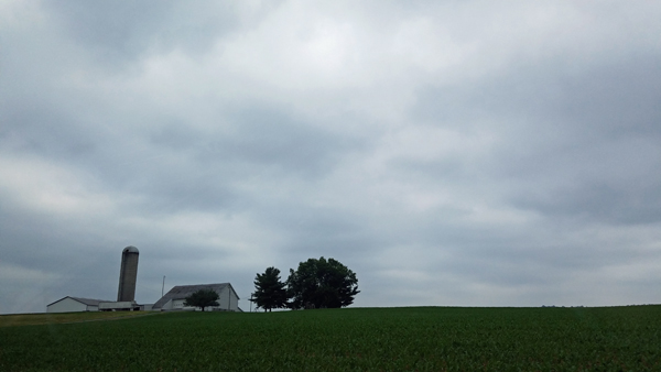 image of a farm atop a green hill, set against a stormy sky