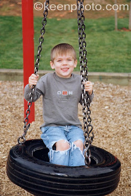 child on tire swing