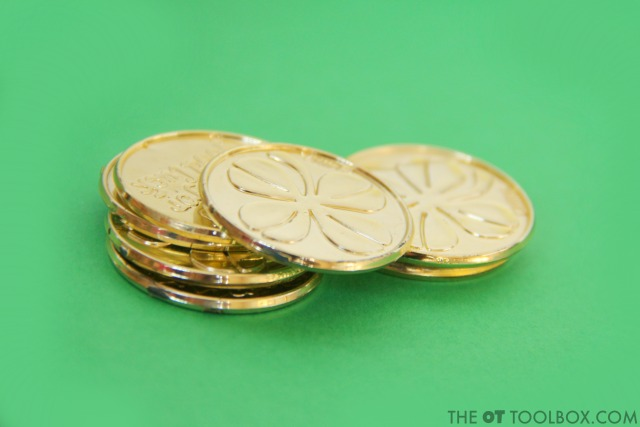 Plastic gold coins (or regular coins) are a great tool for improving hand strength and fine motor skills in kids.