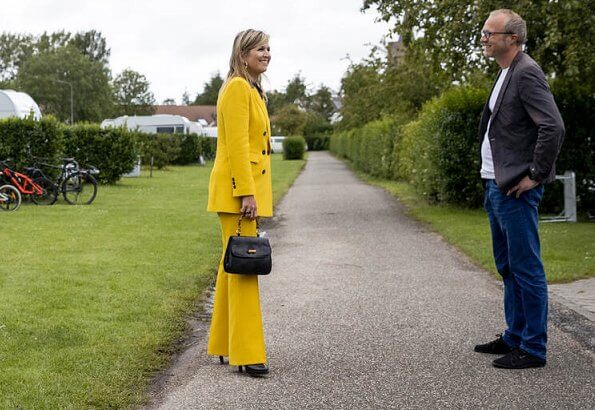 Queen Maxima wore a yellow blazer and trousers from Zara, Cartier gold bamboo earrings, carries Susan Gail bamboo handle handbag