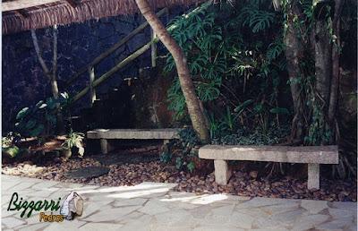 Bancos com pedra folheta de granito no jardim com o piso de pedra.
