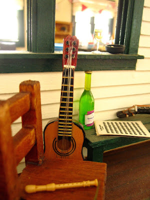 One-twelfth scale miniature veranda scene with a school chair holding a recorder next to a guitar and on a bench next to that a bottle of wine, a stack of sheet music and a ukulele.