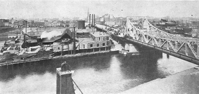 Black and white postcard of bascule bridge spanning industrial waterway with factories and homes accross the creek in the background
