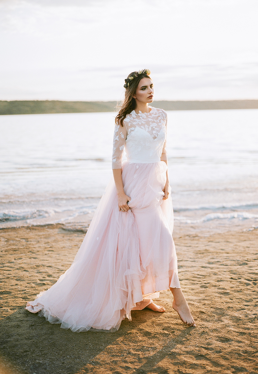This gorgeous blush pink wedding dress is just one of many wedding dresses from She Wore Flowers. This affordable wedding gown has a blush tulle skirt and sheer lace bodice with florals.