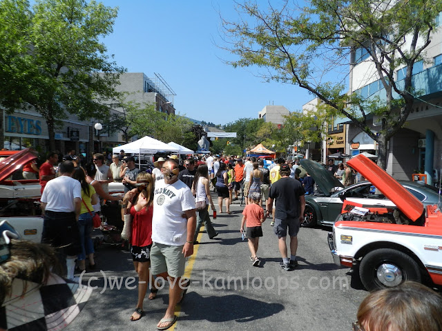 view of the street with the crowd of people looking at the cars of the show