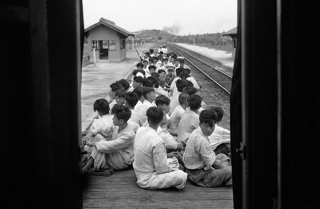 Nuevos reclutas siendo transportados al campo de entrenamiento en un tren sin paredes ni techo
