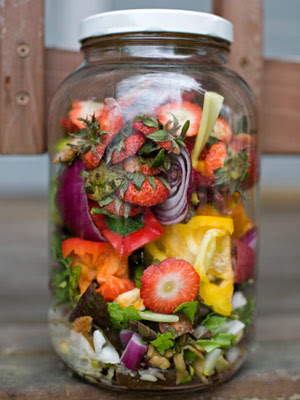 A variety of fruit and vegetable scraps in a large glass jar with a white top