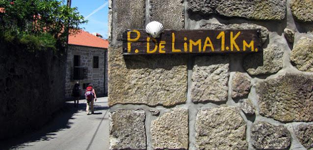 placa indicando 1 km para chegada em Ponte de Lima com a vieira do Caminho de Santiago