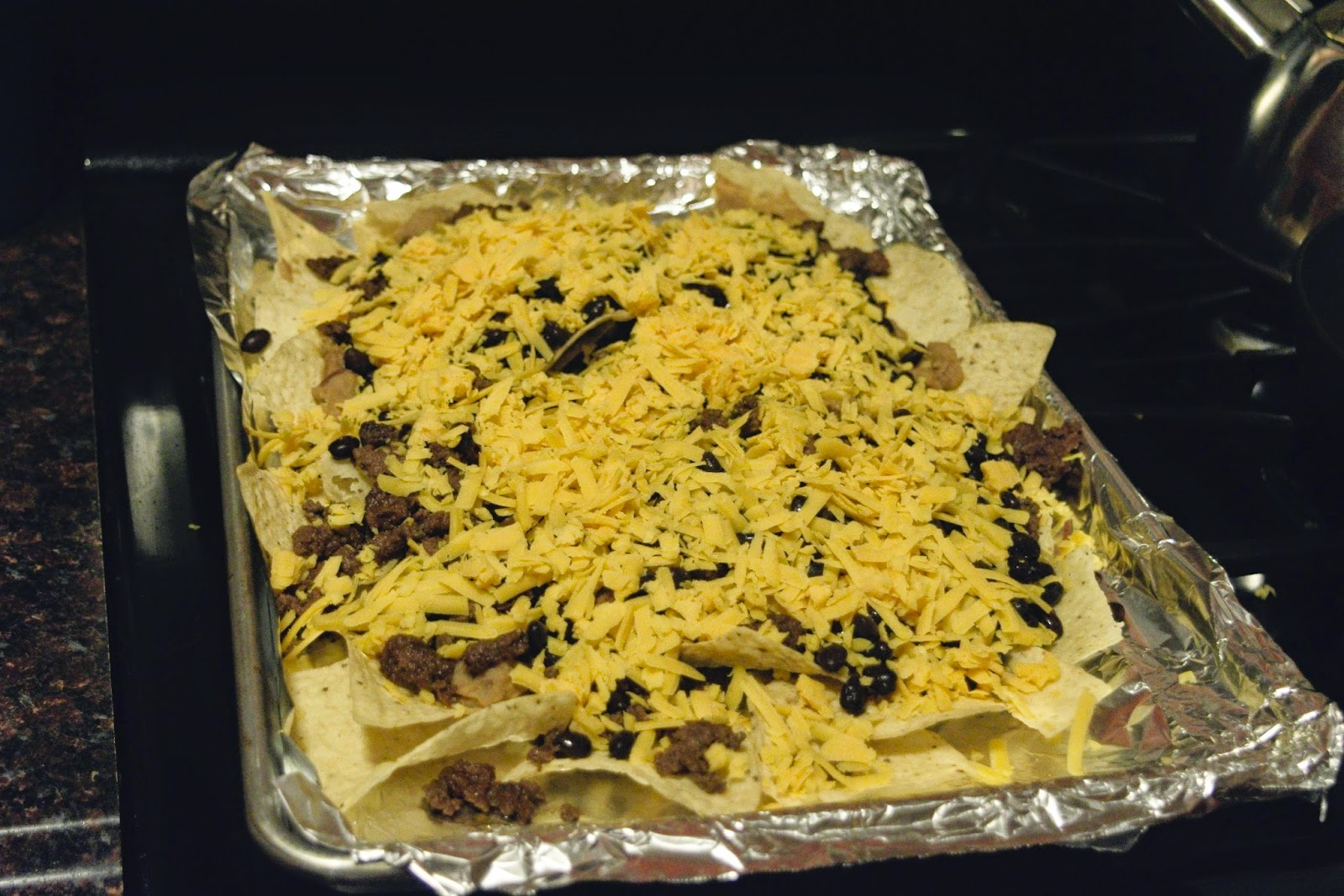 Cheese being added to the Nachos Supreme
