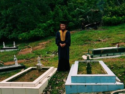 Gadis Berpakaian Wisuda Diantara Dua Makam