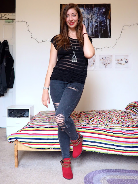 Ruby Red - outfit of black sheer striped top, grey ripped skinny jeans, and red high heeled ankle boots with brown straps