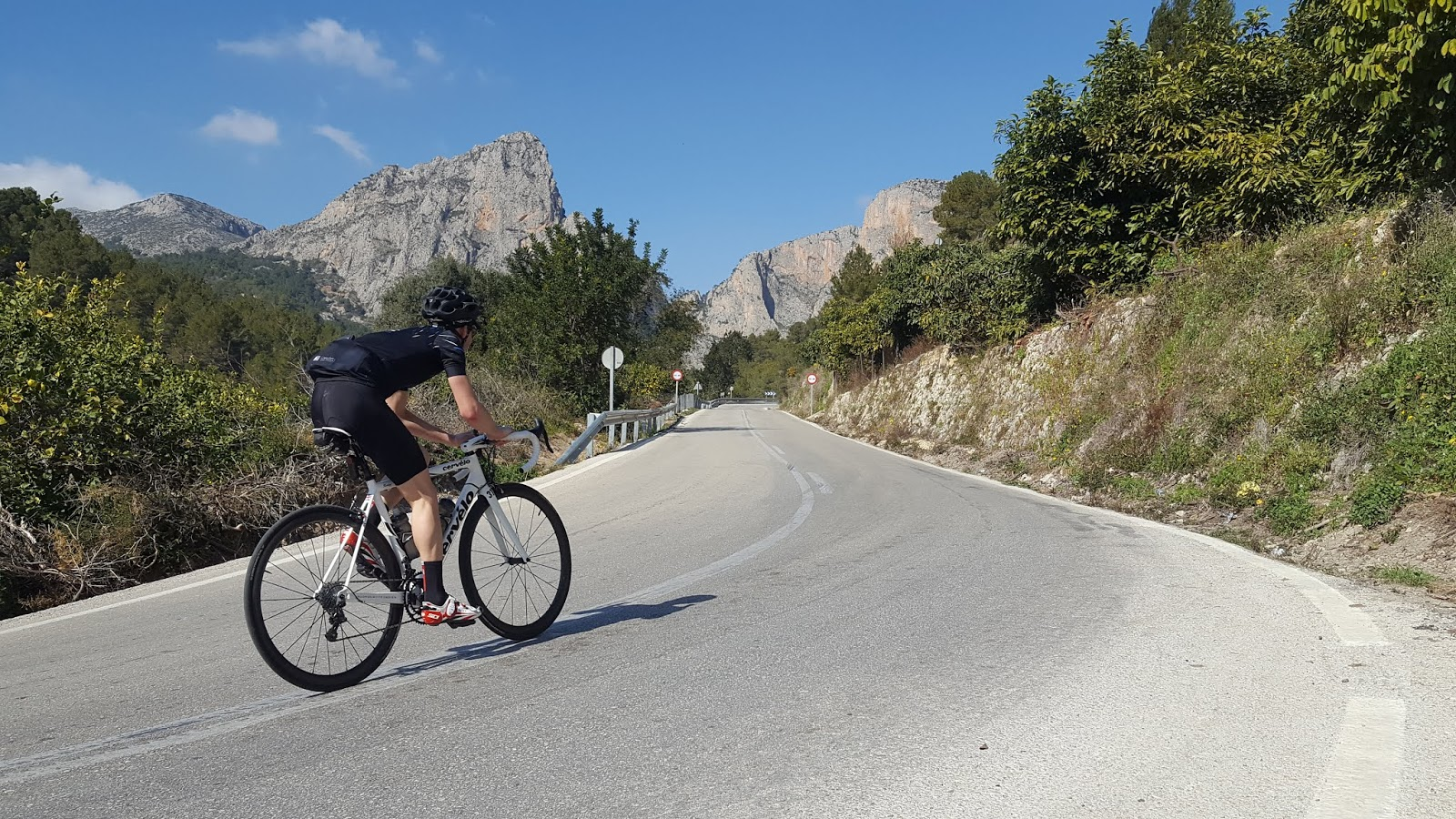 Cyclist climbing south side of Coll de Rates from Callosa d'en Sarria