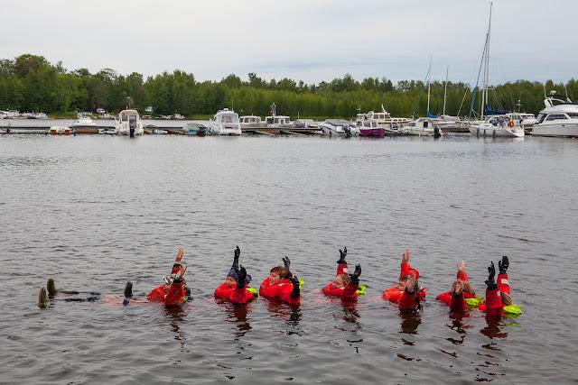 Pelastautumisharjoitus - pitkä jono pelastautumispukuihin pukeutuneita henkilöitä ui vedessä