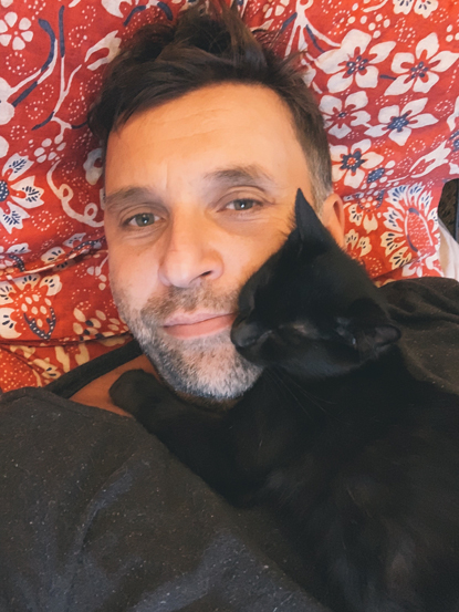 man cuddling black cat