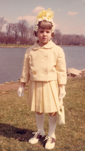 A four-year old Liz, wearing a cute little yellow suit and a hideous daisy-covered Easter bonnet. 1964. Warinanco Park, Union Co. NJ. Collection of E. Ackermann, 2017.