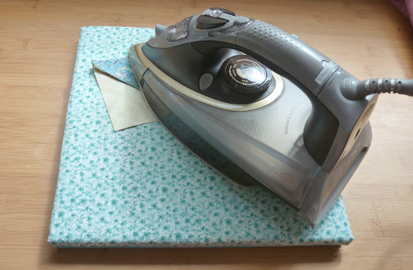 Fabric covered ironing board with iron for sewing craft