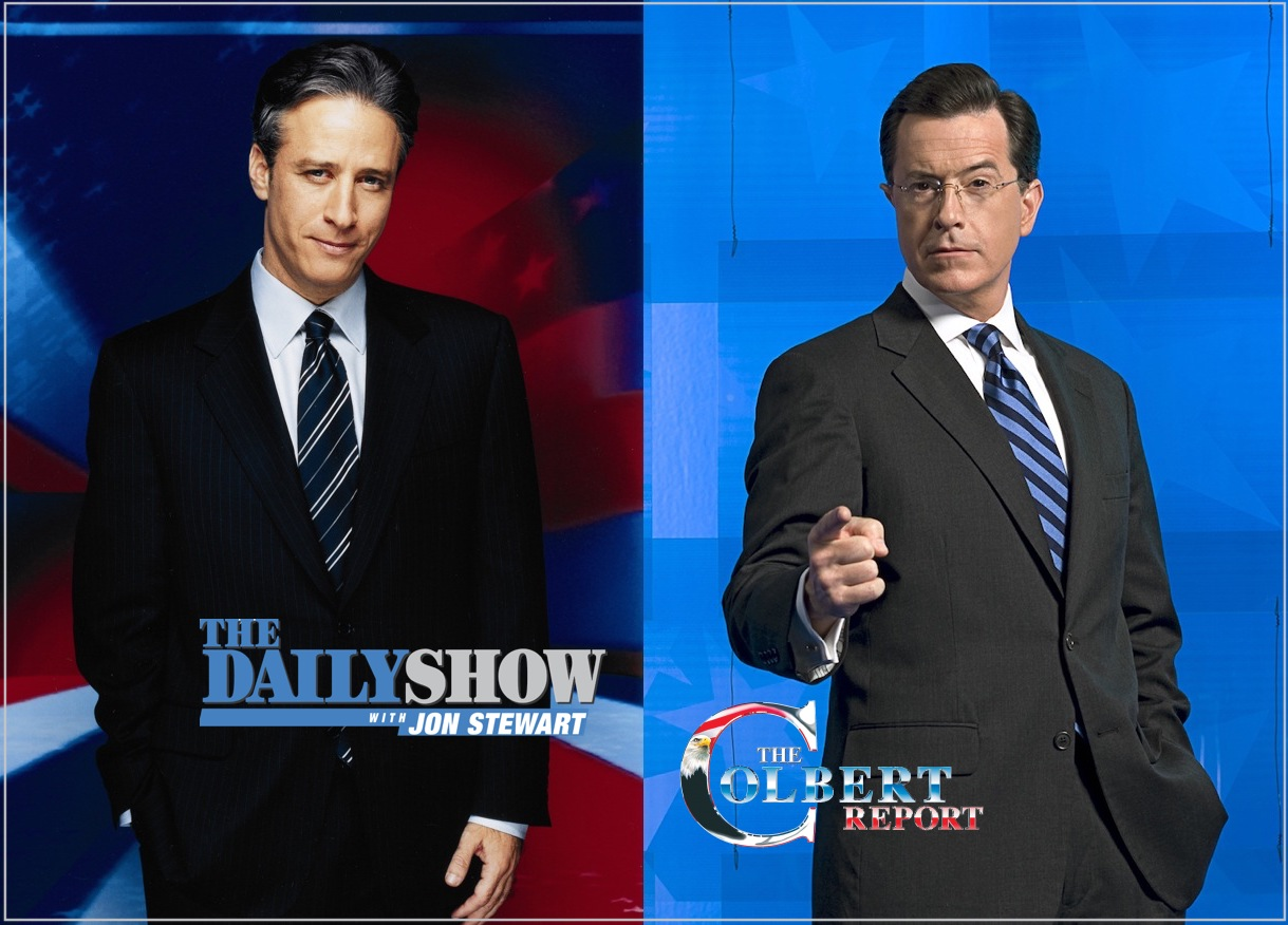 Jon Stewart and Stephen Colbert posing with their show logos